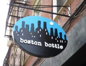 An image showing a bar's sign outside it's building saying Boston Bottle.